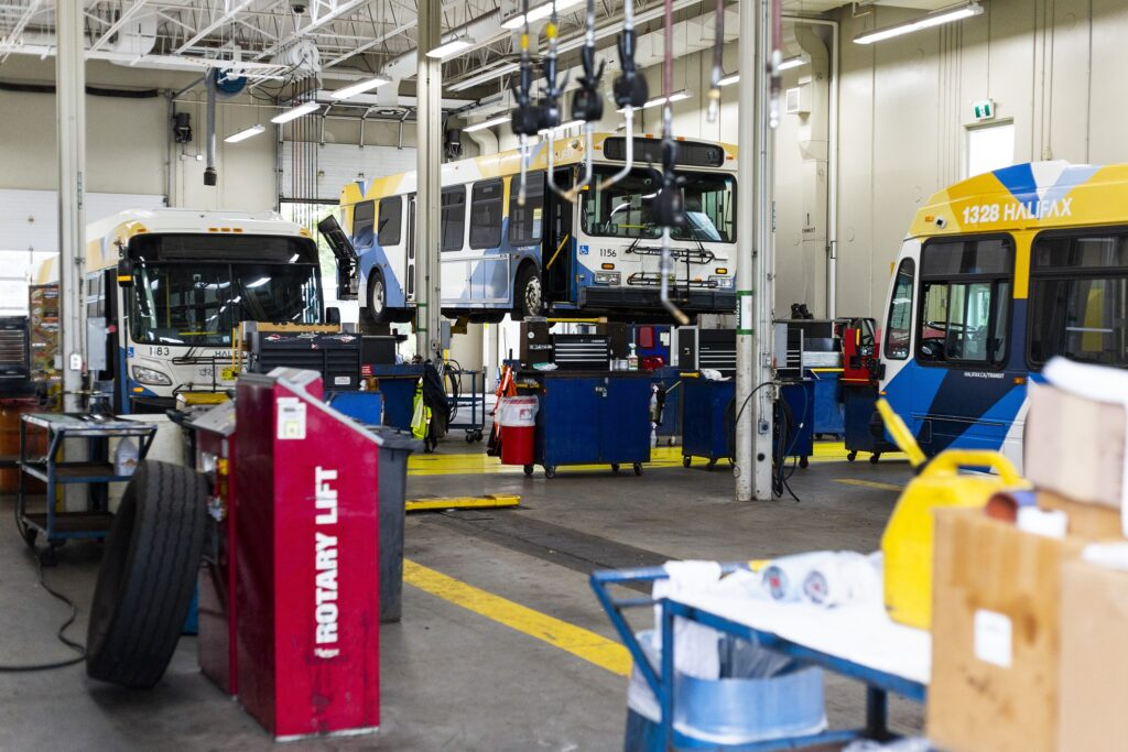 """Three white, blue and yellow buses are seen in a large garage. One bus is on a lift. In the foreground, there's a tire leaning against a red box labeled """"ROTARY LIFT."""""""
