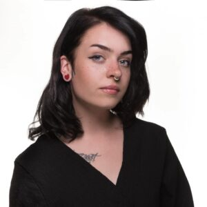 Headshot of woman with shoulder-length brown hair and V-neck top showing part of a tattoo below her right shoulder.