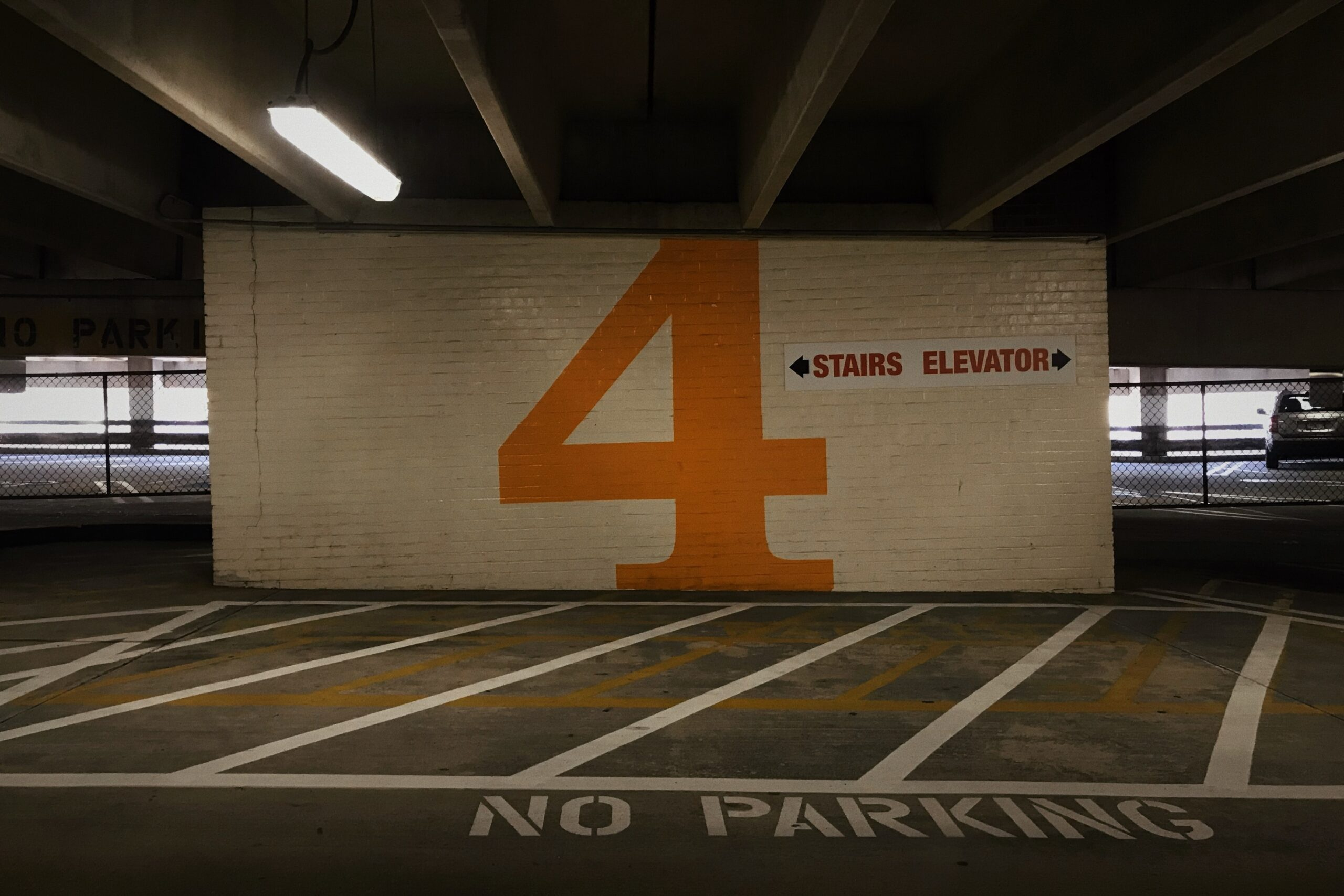 Parking garage with orange number 4 emblazoned on brick wall and words stairs elevator also on wall.