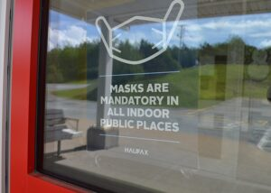 A mandatory mask sign on an outer door.