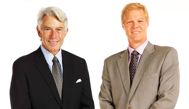 Two smiling middle-aged white guys in suits in front of a white background.