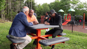 NDP leader Gary Burrill, NDP Preston candidate Colter Simmonds and community activist Quentrel Provo chat at a picnic table.