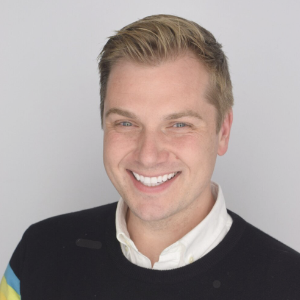 Adam Reid, grinning broadly. he's got short blonde hair, blue eyes, and is wearing a black sweater with blue and yellow trim on the sleeve. His white shirt collar matches his perfect teeth.