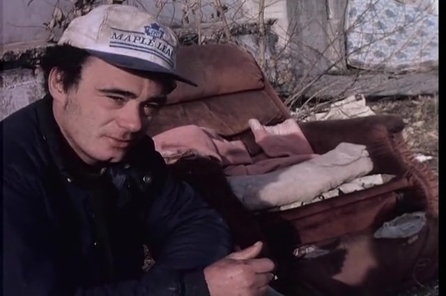 Young man with a somewhat troubled expression, wearing a Toronto Maple Leafs hat. He sits in an abandoned lot with debris or garbage around him, including pieces of broken furniture.