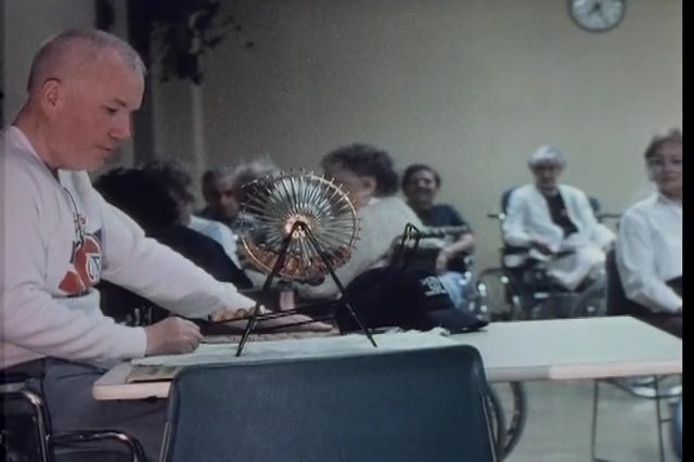Man in a Montreal Canadiens shirt calling a bingo game in an institutional room with people wearing hospital gowns in the background