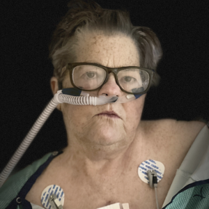 Jane Kansas, shown with a breathing tube in her nose, and two EKG wires taped to her upper chest.