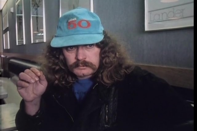 Man with long curly hair and a droopy moustache sitting on the floor, and wearing a Labatt 50 cap.
