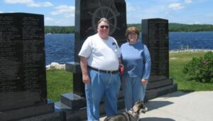 Tom and Diane Ledvina in front of a set of monuments on a sunny summer day. They look happy.