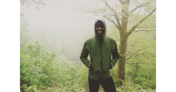 Chúk Odenigbo, a smiling young Black man standing in the woods on a misty day. He is wearing a rain jacket with its hood pulled up and has his hands in his pockets.