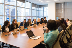 A large group of people, mostly Black women, meet around a large table in a light-filled office