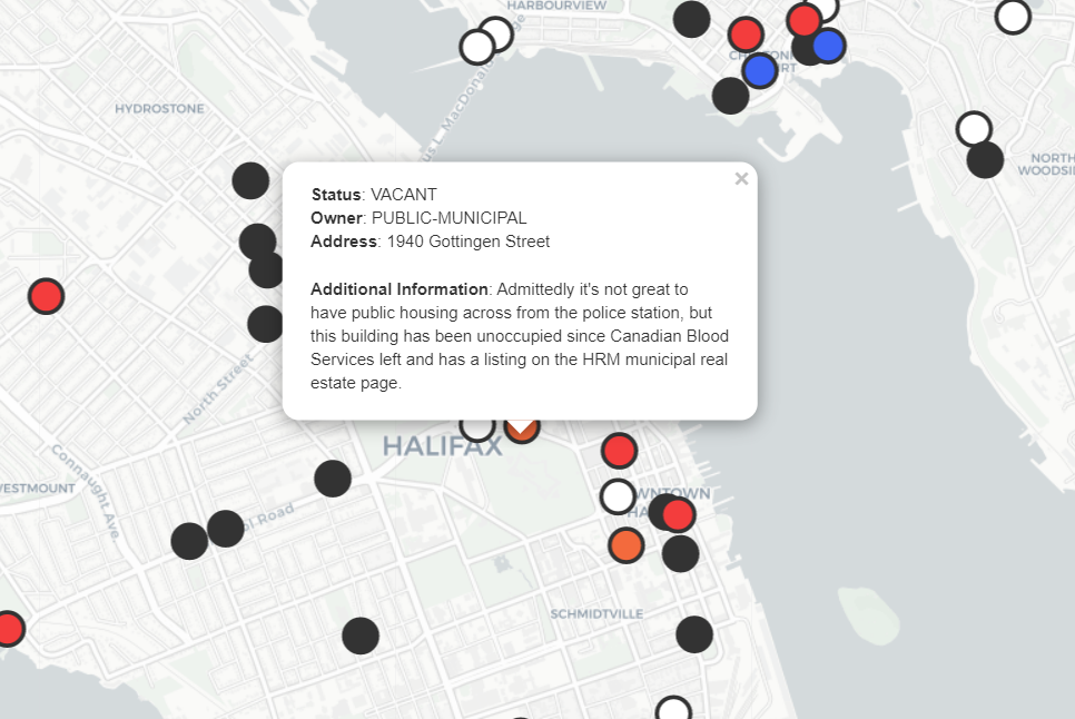 Map showing parts of downtown Halifax and Dartmouth with circles representing vacant or unused land and buildings. An open popup reads: Admittedly it's not great to have public housing across from the police station, but this building has been unoccupied since Canadian Blood Services left and has a listing on the HRM municipal real estate page.