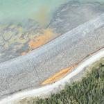 An aerial shot of a bright yellow pool of tailings that appear to be leaking out of a storage pond.