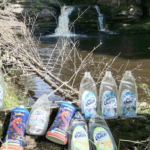 Empty dish soap bottles lined up in front of a pristine waterfall.