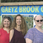Three women standing in front of the Gaetz Brook Greenway sign.