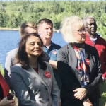 A handful of the Liberal candidates standing in front of a lake.