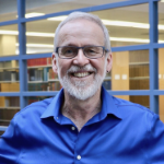Wayne MacKay, smiling broadley in a royal blue shirt