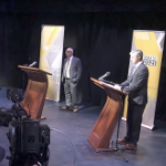 Candidates stand at their podiums in a television studio