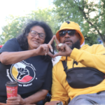 A Black man and an Indigenous woman wearing a ribbon skirt make a hand gesture together.