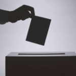 A ballot going into a box.
