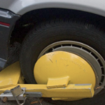 A yellow mechanical boot clamped to a car's wheel