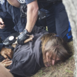 A man is held face-down on the ground by several cops
