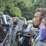 Two male protesters, one wearing a mask, are shown facing a line of police in full riot gear