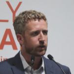 Iain Rankin speaking into two microphones