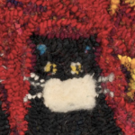 One of the black kitties wearing a white mask in Laura Kenney's hooked rug