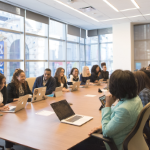 A group of mostly Black people around a large meeting table in a light-filled office.