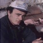 A man wearing a ball cap sits near some broken-down furniture