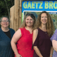 The five ladies who started WAVES, in front of the Gaetz Brook Greenway sign