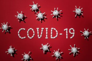 COVID 19 spelled out in white pills, with viruses made from styrofoam balls with swabs stuck in them. All on a red background.