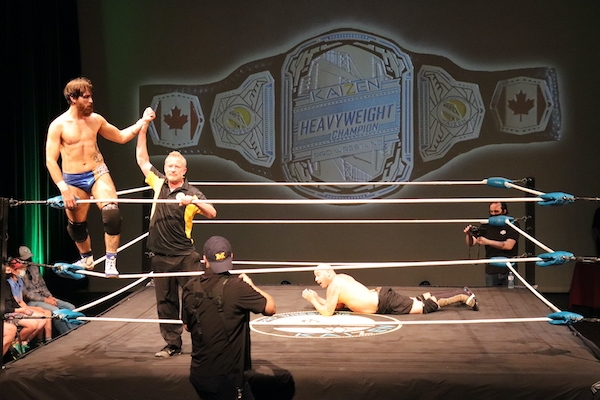 Covey Christ stands on the ropes with his hand held aloft by the ref. Covey is wearing shiny speedo style briefs that are half white and half blue, black knee pads, and white wrestling shoes that come to above the ankle. The ref is wearing black pants and a black short-sleeved collared golf shirt with yellow panels down the sides. JP Simms lies inside the ring, looking on in disbelief. He's shirtless, with black knee-length shorts with green camouflage trim, black knee pads, and what look like long wrestling boots which come up to his knees.