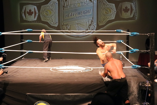 The ref is on the other side of the ring with his back turned. JP Simms is outside the ring, and Covey Christ is in the ring directly front of him, grabbing on to the middle rope as he falls.