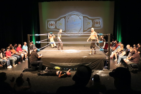Covey Christ is in the corner on his knees, and the ref is in the center of the ring looking toward Simms, who's looking at the other ref on the floor outside the ring
