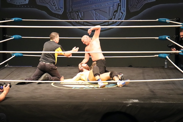 the ref and Simms are both on their knees, and Covey Christ is on his back waiting for the punch to land