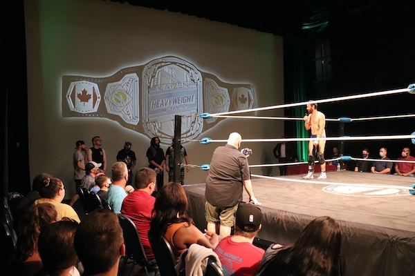 Covey christ stands in the ring with a microphone, looking exhausted