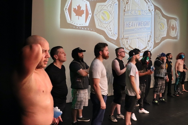 A lineup of the men outside the ring, with a shirtless JP Simms in the foreground