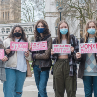 Seven young women hold signs protesting sexual and street harassment in London.