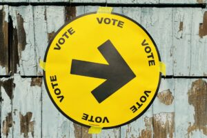 A circular yellow sign with a black arrow and the word VOTE printed six times around the circle is seen taped to weathered blue-green cedar shingles.