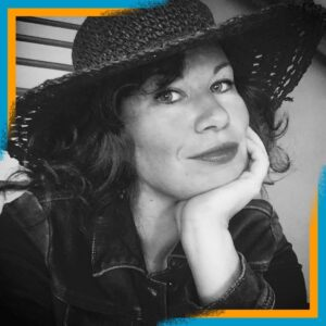 A black and white photo of Jill Chandler, looking very stylish in a denim jacket and black straw hat with a wide brim