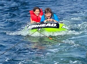 A photo of Maggie and Zack on a tube in the water being pulled by a boat.