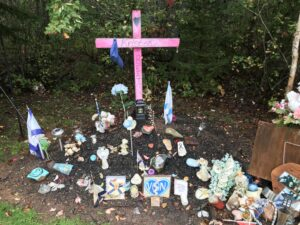 A roadside memorial for Kristen Beaton who was killed in the April 2020 shooting in Nova Scotia. The memorial is a pink cross surrounded by flowers, photos, Nova Scotia flags, and painted rocks.
