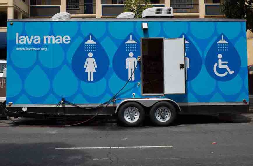 """A blue trailer is shown parked on the street. It says """"lava mae"""" and has male, female and accessible washroom symbols with drawings of showers above each of them. There's a door open, and wiring plugged into the trailer."""