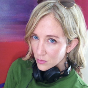 Sheri Elwood, a blond woman wearing a green top, with sunglasses on her head and black headphones around her neck.