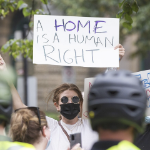 A protestor holds a sign which reads a home is a human right.