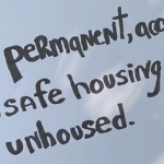 A close up of a cardboard sign with the words permanent, safe housing, and unhoused on it.