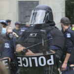 A very intimidating cop wearing full body armour and a helmet with the visor down, carrying a shield and baton.