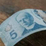 A Canadian five dollar bill on a hardwood floor