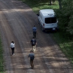 An aerial shot of four people taking video footage on a dirt road